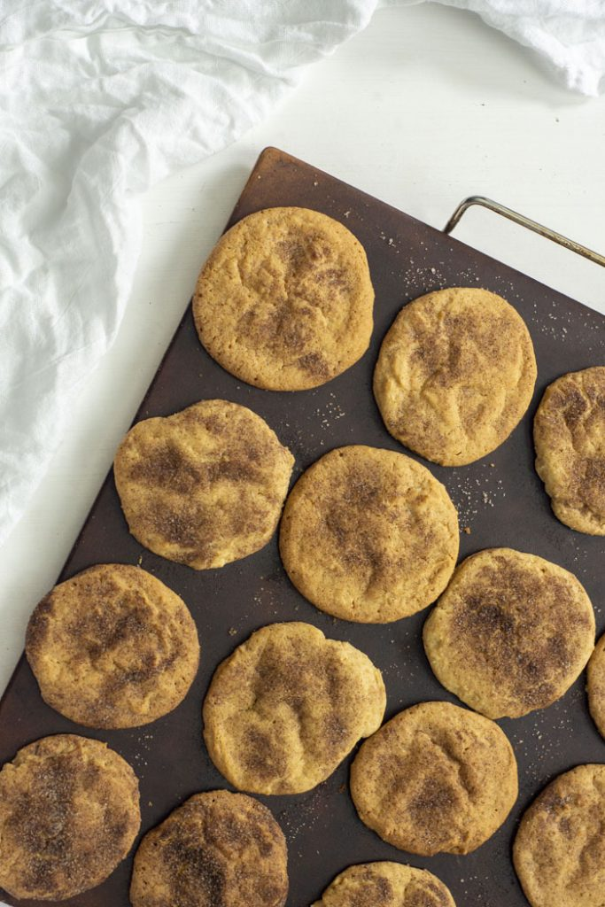 Baked Cinnamon Sugar Cookies on a baking stone with a white towel behind on a white surface (vertical)