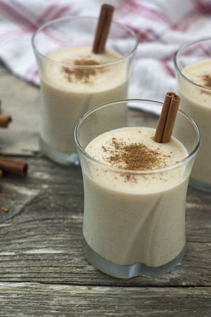Three glasses filled with coquito and topped with cinnamon with a cinnamon stick inside each next to a few extra cinnamon sticks with a white and red towel behind all on a wooden surface (vertical)