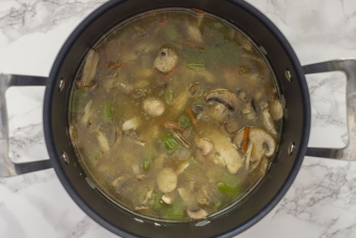 Large stockpot with prepared vegetables and mushrooms cooking in chicken broth on a white and grey marble surface