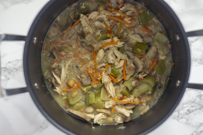 Large stockpot with prepared vegetables, mushrooms, shredded chicken, and chickpeas cooking in chicken broth on a white and grey marble surface