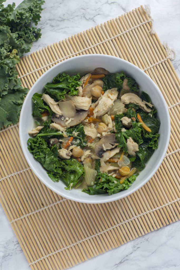 Immunity Soup: Cooked broth with vegetables, chicken, chickpeas, and kale in a round white dish on a bamboo mat next to raw kale on a white and grey marble surface (vertical)