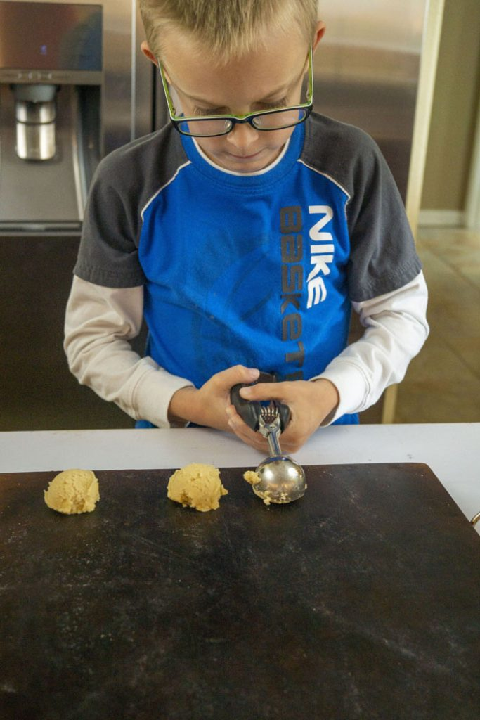 Young boy using a cookie scoop to place cookies on a baking stone on top of a white surface