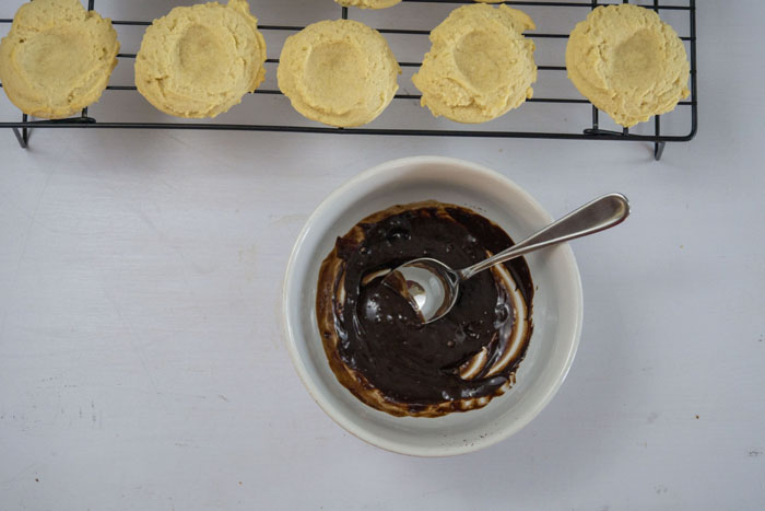 Round white bowl with melted chocolate in front of baked thumbprint cookies on a wire cooling rack all on a white surface