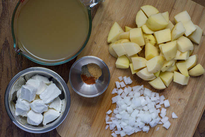 Bamboo cutting board with diced potatoes, diced onion, and a small stainless steel bowl of spices next to a large glass measuring cup of broth and a stainless steel bowl of cream cheese all on a wooden surface