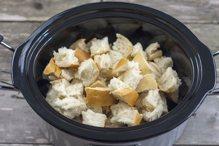Slow cooker filled with chunks of bread on a wooden surface