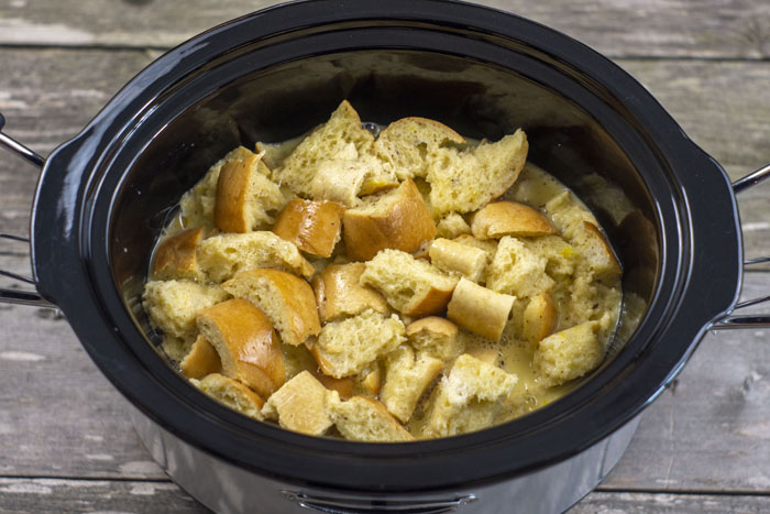 Chunks of bread covered with egg and milk mixture in a slow cooker on a wooden surface