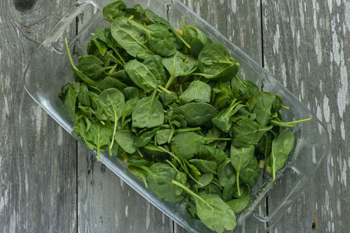 Glass baking dish filled with spinach leaves on a wooden surface