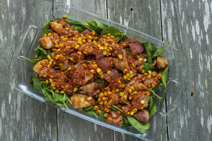 Cooked potatoes, tomato sauce, diced onions, and corn kernels on top of a bed of spinach leaves in a glass baking dish on a wooden surface