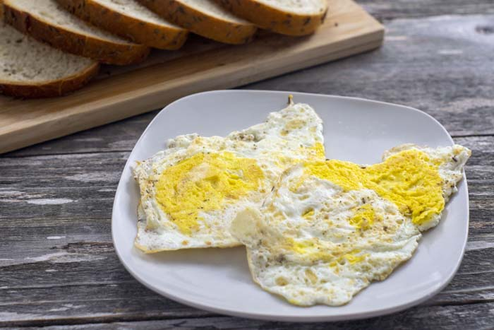 Square white plate with fried eggs over hard next to a bamboo board with sliced bread all on a wooden surface