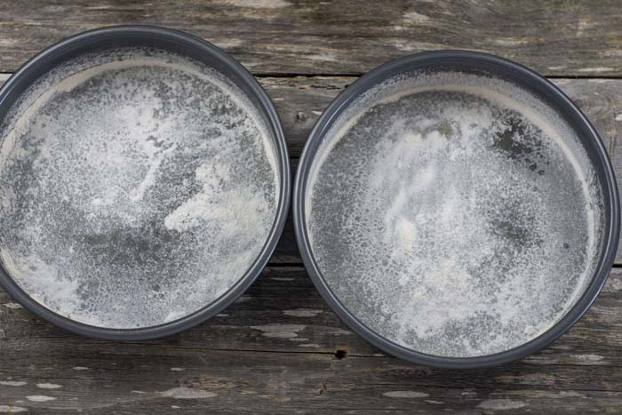 Two round metal cake pans that have been greased and floured on a wooden surface