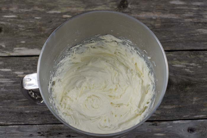 Large mixing bowl with cream cheese frosting on a wooden surface