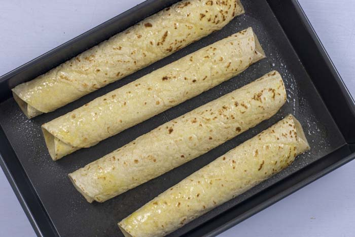 Rectangular metal baking dish with rolled up taquitos covered with oil on a white surface