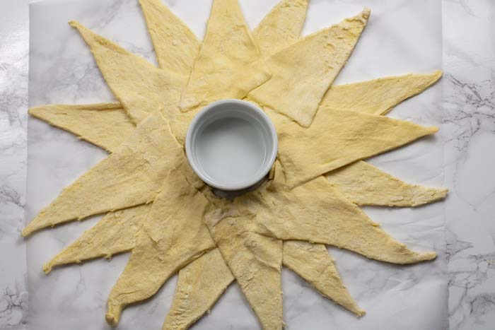Small white ramekin surrounded by crescent rolls laid out in a star shape on a piece of parchment paper over a white and grey marble surface