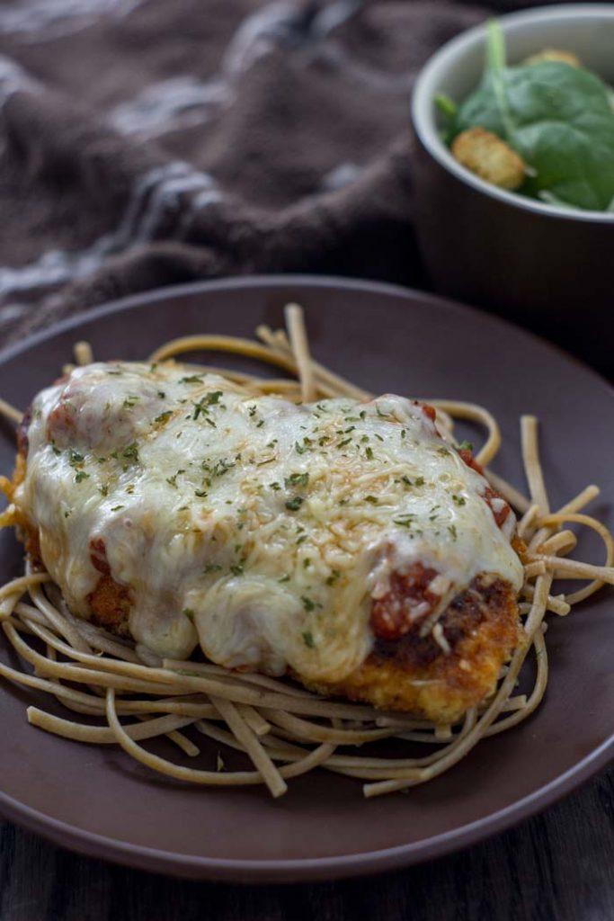 Chicken parmesan on top of a bed of noodles on a round brown plate with a white bowl of salad and a brown and white towel behind all on a wooden surface (vertical)