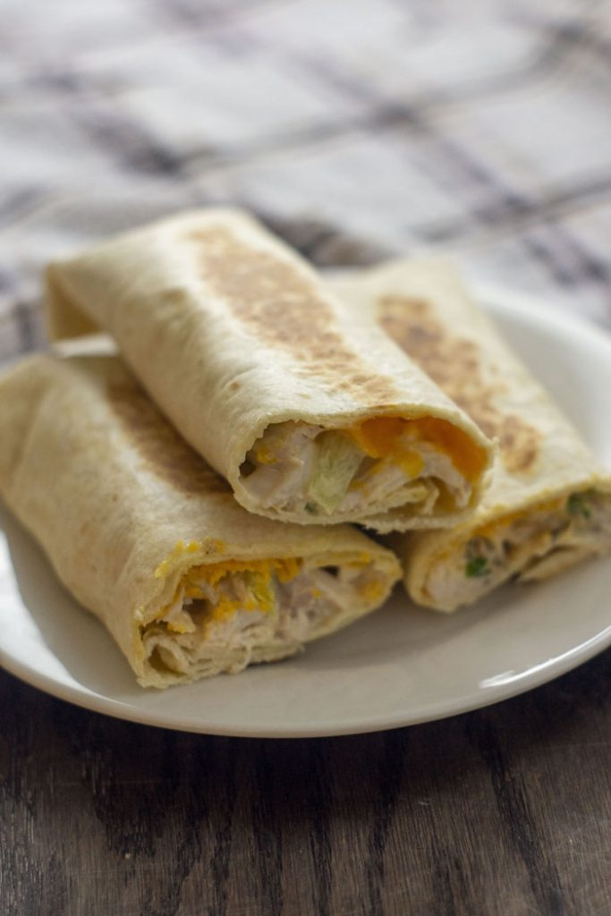 Side view of three crispy chicken wraps with the ends cut off to show the cheese and chicken mixture inside stacked on a small white round plate with a white and brown towel behind all on a wooden surface (vertical)