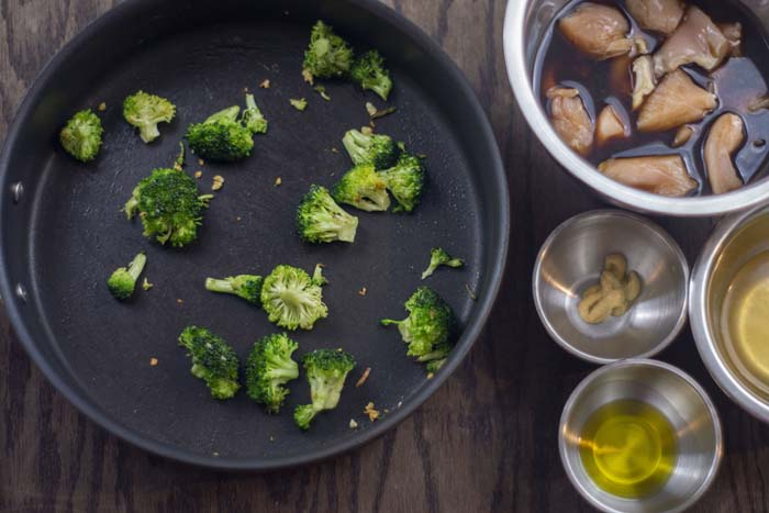 Skillet with roasted minced garlic and broccoli next to stainless steel bowls with chicken marinading in soy sauce, dijon mustard, oil, and chicken broth all on a wooden surface