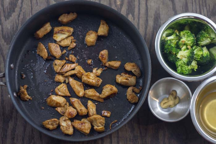 Skillet with cooked chicken next to stainless steel bowls of roasted chopped broccoli, dijon mustard, and chicken broth all on a wooden surface