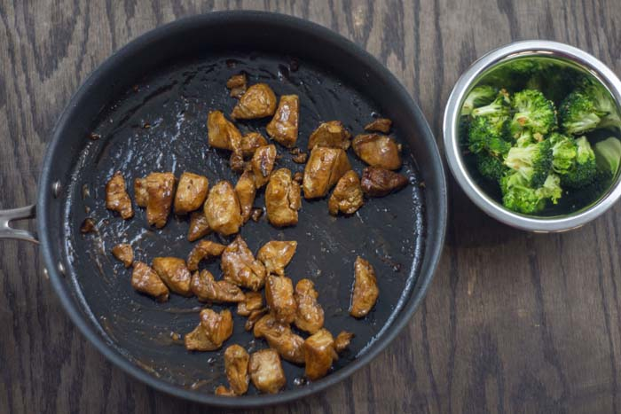 Skillet with cooked chicken in chicken broth and dijon mustard next to a stainless steel bowl of roasted garlic and broccoli all on a wooden surface