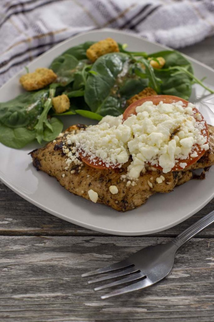 Feta-topped chicken on a square white plate next to a salad with a fork in front and a white and brown towel behind all on a wooden surface (vertical)