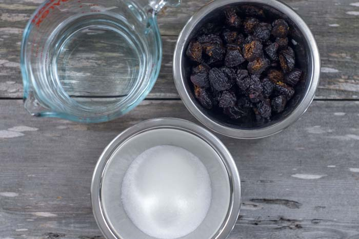 Glass measuring cup with water next to stainless steel bowls of chopped dried figs and sugar all on a wooden surface