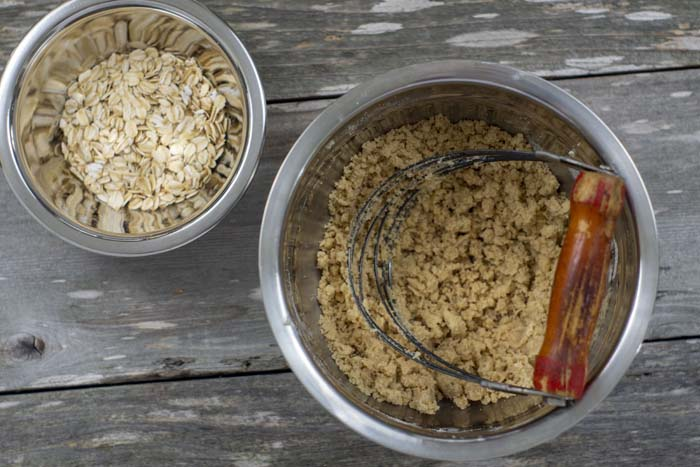 Stainless steel bowl of oats next to another stainless steel bowl of streusel with a pastry blender in the bowl all on a wooden surface