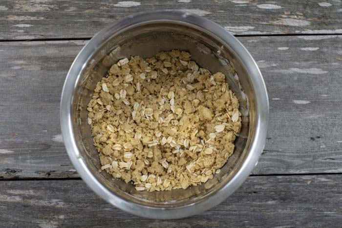 Stainless steel bowl with mixed streusel topping on a wooden surface