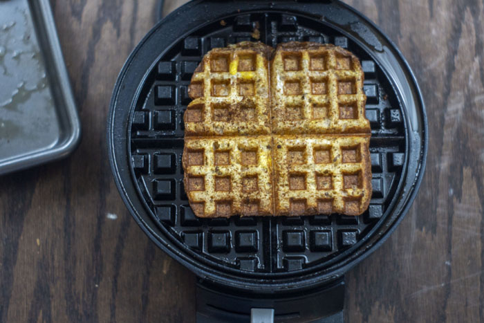 Open waffle iron with a piece of cooked french toast on top next to an empty metal baking sheet on a wooden surface