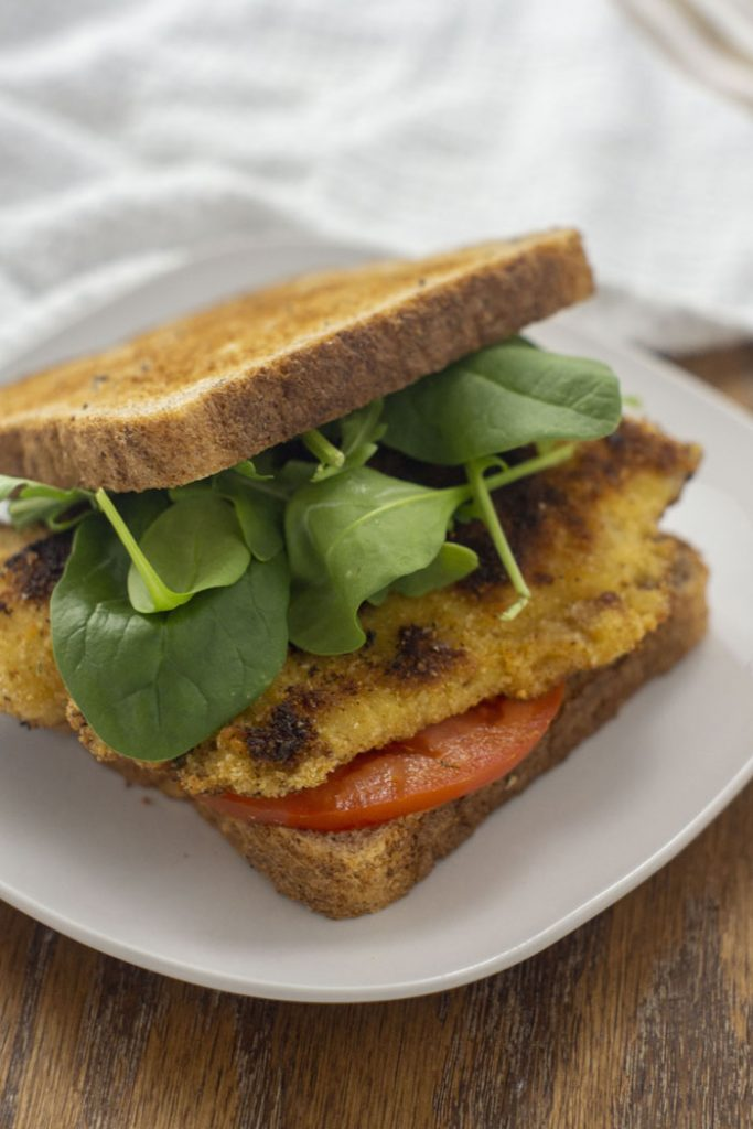 Fried tilapia sandwich wiht sliced tomato and fresh spinach on a square white plate with a white towel behind on a wooden surface (vertical)
