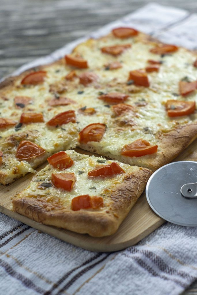 Mozzarella-Topped Flatbread on a bamboo cutting board with one square corner piece cut out next to a metal pizza cutter on a white and brown towel (vertical)