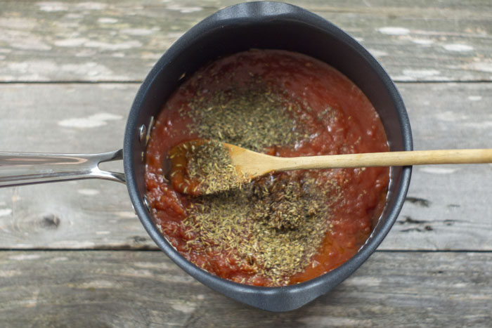 Tomato sauce covered with seasonings with a wooden spoon in a saucepan on a wooden surface