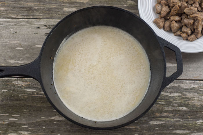 Gravy ingredients in a cast iron skillet next to a round white plate with cooked sausage on a wooden surface