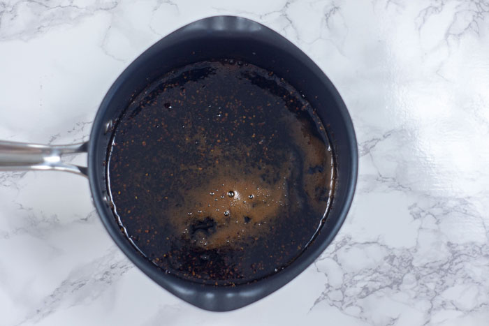 Medium saucepan with soy-molasses glaze over a white and grey marble surface