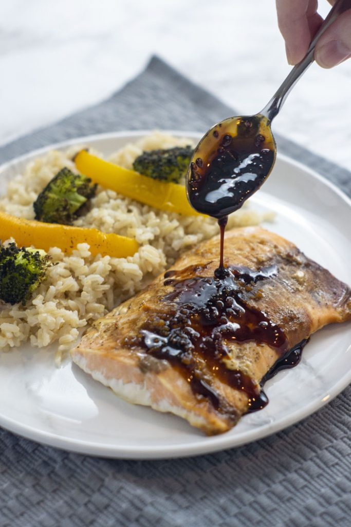 Woman's hand holding a spoon with soy-molasses glaze dripping onto a fillet of cooked salmon next to a bed of rice with roasted yellow bell pepper and broccoli on a round white and grey marbled plate on top of a grey placemat on a white and grey marbled surface (vertical)