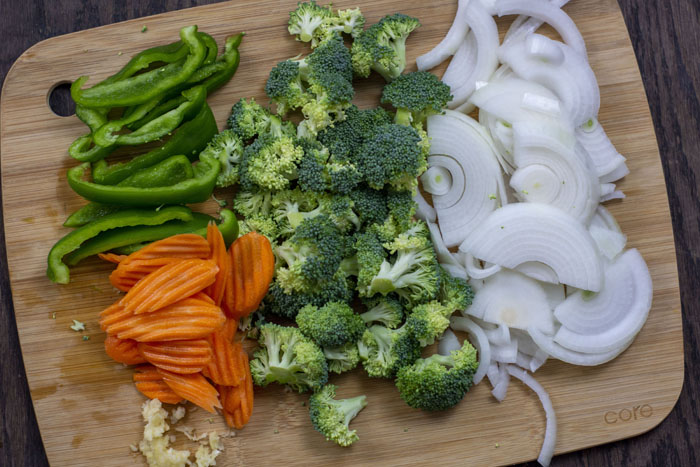Bamboo cutting board with sliced green pepper, carrots, onion, minced garlic, and chopped broccoli