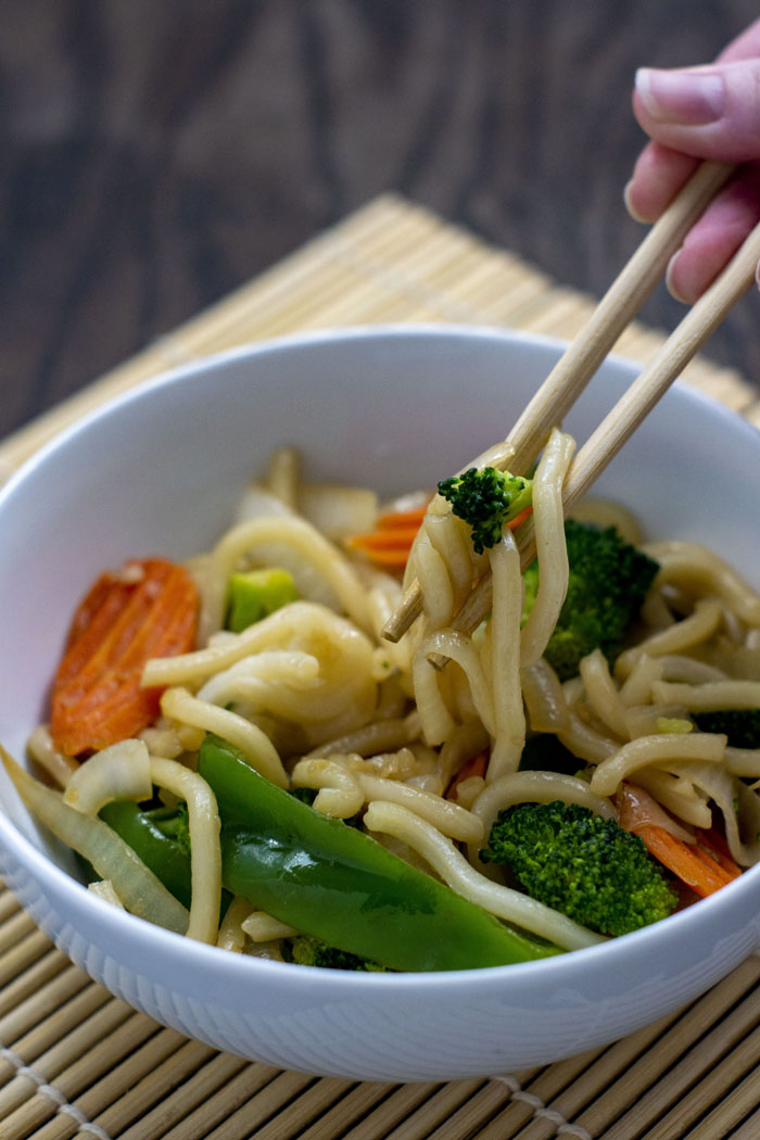 Round white bowl of vegetable lo mein with a pair of chopsticks pulling out some noodles, onion, and broccoli on top of a bamboo placement on a wooden surface (vertical)
