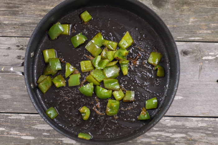 Cooked diced green peppers in a large nonstick skillet over a wooden surface