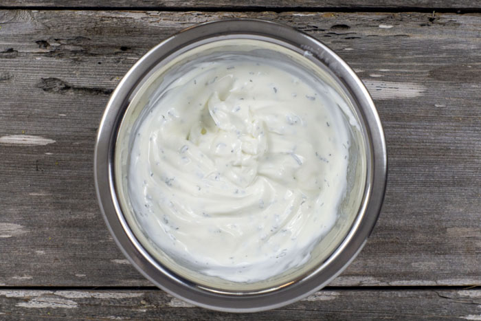 Sour cream mixture in a stainless steel bowl on a wooden surface