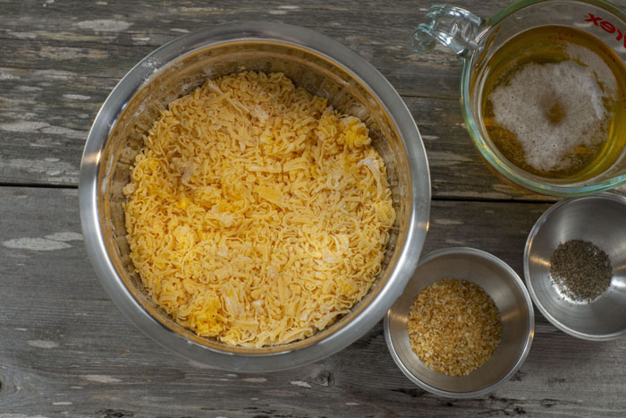 Stainless steel bowls with shredded cheddar cheese mixed with flour, pepper, and minced garlic and a glass measuring cup with beer all on a wooden surface