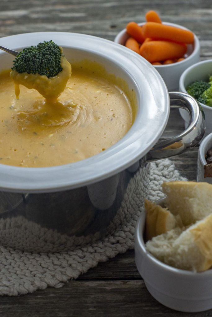 White and stainless steel fondue pot on top of a white knit potholder filled with garlic and herb cheese fondue with a piece of broccoli being dipped in the cheese next to white bowls with carrots, broccoli, beef tips, and bread all on a wooden surface (vertical)