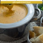 Garlic and Herb Cheese Fondue in a white and metal bowl surrounded by dippers (with title overlay)
