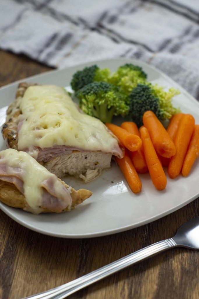 Cut piece of chicken cordon bleu with fresh carrots and broccoli on a square white plate with a stainless steel fork in front and a white and brown towel behind all on a wooden surface (vertical)