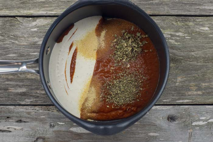Marinara sauce, ranch dressing, and seasonings in a sauce pan on a wooden surface