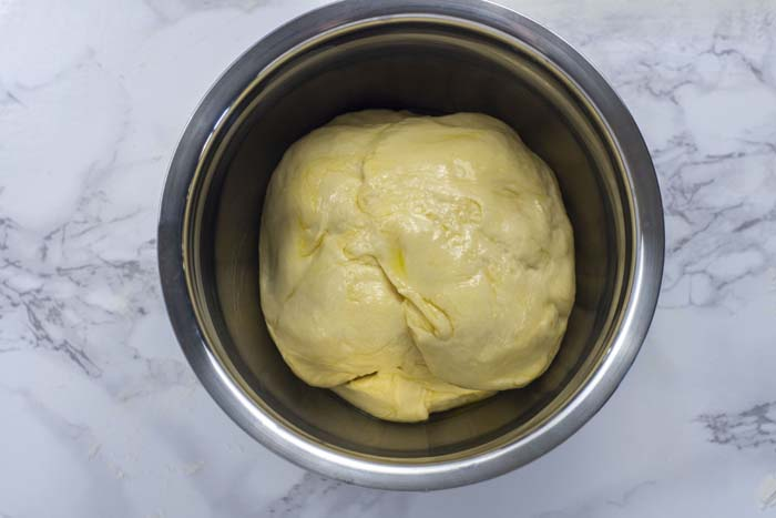 Kneaded dough covered in oil in a stainless steel bowl on a white and grey marble surface