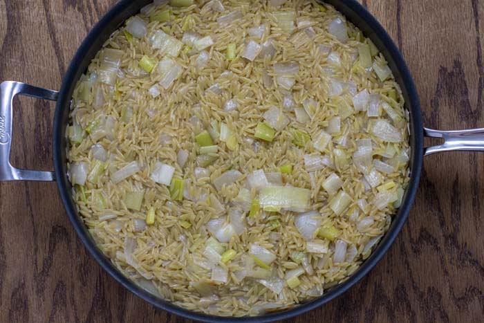 Diced yellow onion and diced leek with orzo in white wine, butter, and olive oil covered with vegetable broth in a large nonstick skillet over a wooden surface