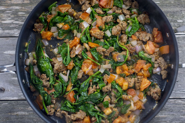 Cooked sausage with wilted spinach and diced tomatoes and onions in a large nonstick skillet on a wooden surface