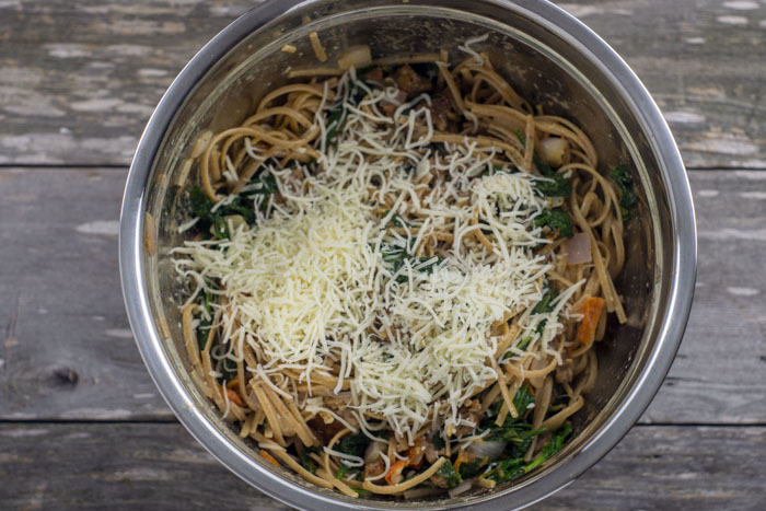 Spaghetti noodles mixed with sausage, spinach, onions, and tomato topped with shredded cheese in a stainless steel bowl on a wooden surface