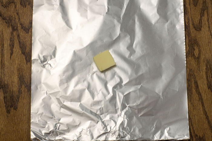 A pat of butter on an aluminum foil sheet on a wooden surface
