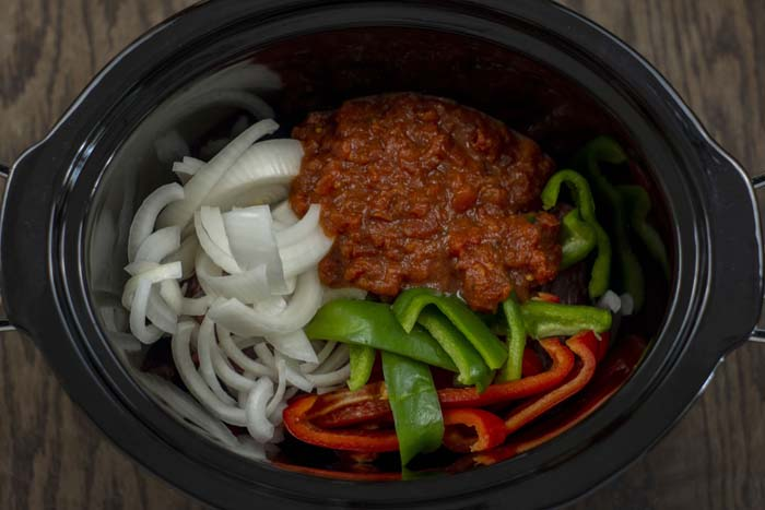 Overhead view of steak strips topped with sliced white onion, green bell pepper, red bell pepper, and salsa in a slow cooker on a wooden surface
