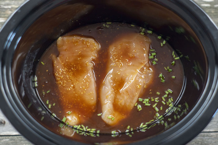 Chicken covered with sweet and sour sauce and chopped green onions in a slow cooker on a wooden surface