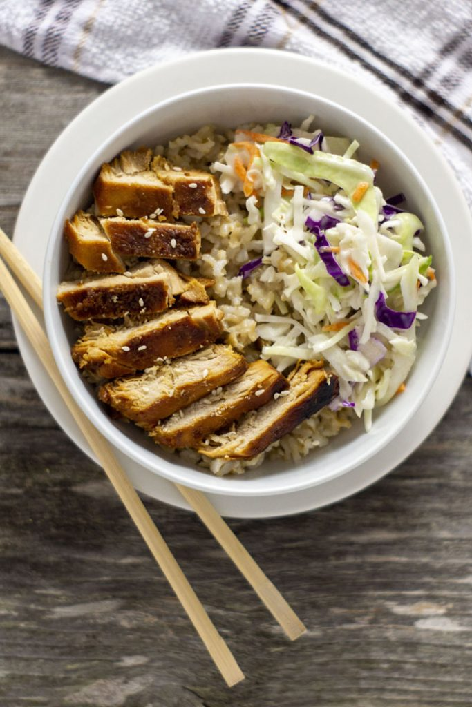 Sweet and sour chicken in rice with a scoop of coleslaw in a white round bowl on top of a white round plate with bamboo chopsticks on the plate and a white and brown towel behind all on a wooden surface (vertical)